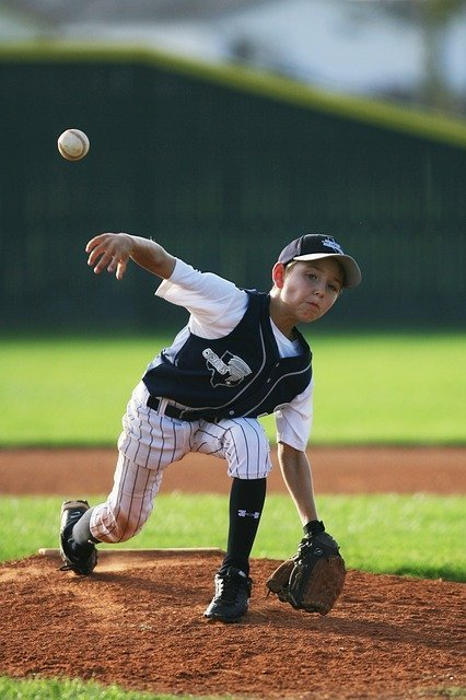 youth baseball pitcher releasing a pitch-curveball